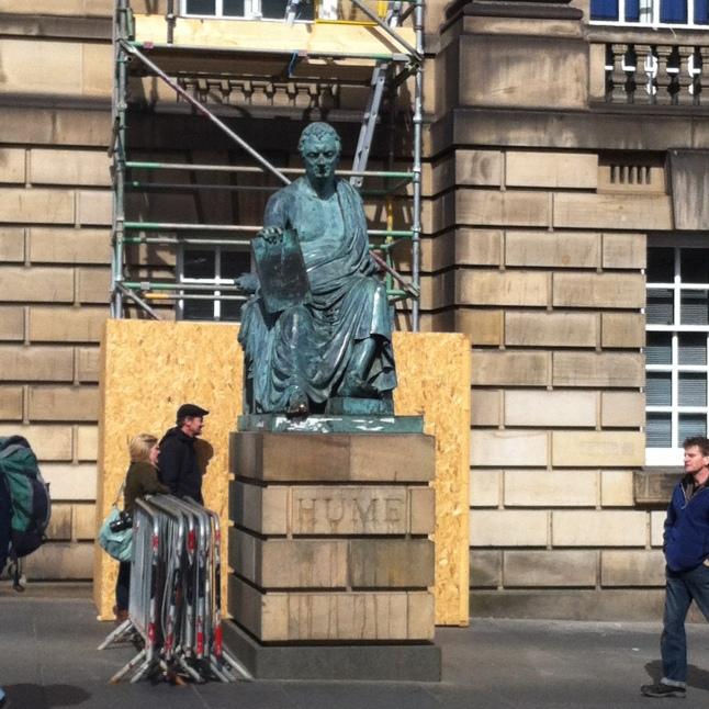 Dit is David Hume. Tegenover zijn standbeeld is er een plek waar je op moet spuwen om de slechte toverkollen die vroeger de stad teisterden met hun hekserij buiten te houden